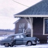 Vernon River 1967. Photographer unknown. It looks like the door is removed at this point; too bad the car is in the way. The proportions of the removed door seem correct for it to be resting on the ground right where the car's roof is. That would indicate that the earth is built up to the foundation's top.